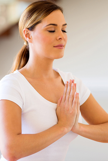 Woman claspping hands over heart chakra